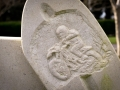 Detail of a motorbike from a bespoke, horseshoe-shaped headstone, carved in Portland stone for a customer.