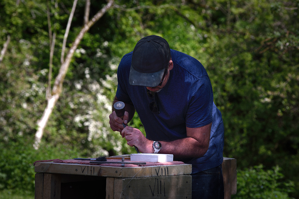 A student carving stone.