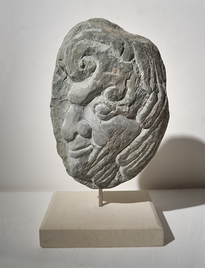 Green slate face, carved from a large pebble by Jonathan Sells. £200.